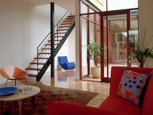 Living Room with Red Sofa and Modern Staircase
